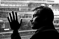 Man gazing out rainy window